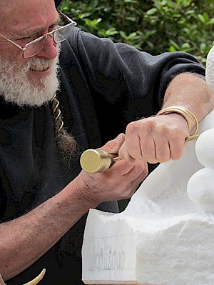 Fisher delicately chisels into a piece at the 2014 Art in the Gardens