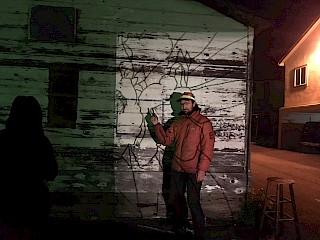 The artist started by projecting a sketch onto the side of the building at night and tracing it with charcoal. gallery image